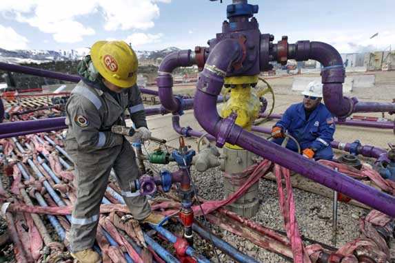 Workers tend to a well head during a hydraulic fracturing operation in western Colorado, March 29, 2013. (AP Photo/Brennan Linsley)